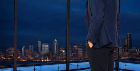Back of businessman in suit standing at the window of Seattle downtown Washington, USA