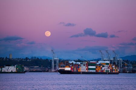 Cargo ship with containers in Seattle port at night over lune in the sky, Washington, USA