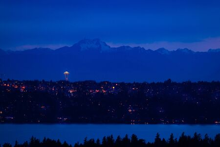 View of Seattle town at night and mountain Olympus on background with homes, lake Washington in front from Bellevue, WA, USA