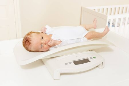 Little baby boy lay on the scale for measuring body weight in nursery room