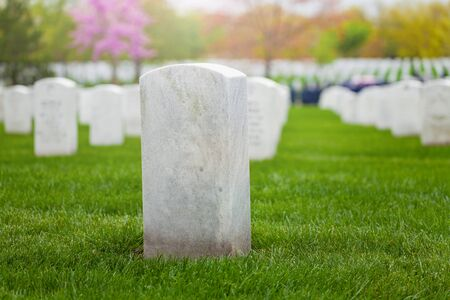 White tombstone on the lawn of military cemetery in a row of graves Stock Photo