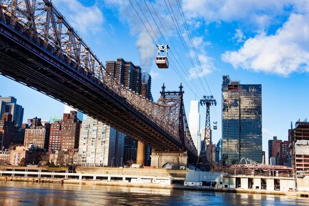East river with Roosevelt Island tramway system and Ed Koch Queensboro Bridge over New York buildings, NY, USA