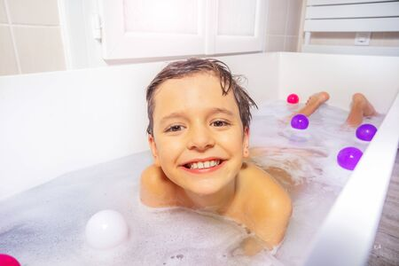 Portrait of a boy play with toys and soap on the belly in the bath water at home