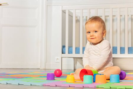 Baby toddler boy building pyramids on the carpet in nursery by the child crib with calm face expression