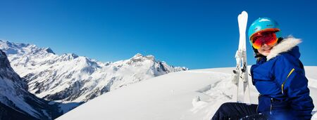 Wide panorama of mountains with the girl in blue helmet and ski outfit over the sky sit in snow on alpine resort