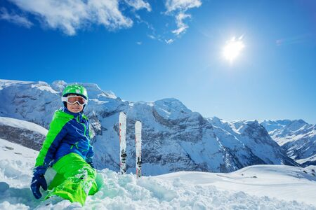 Little boy having fun skiing in Alpine mountains portrait with panorama copy space