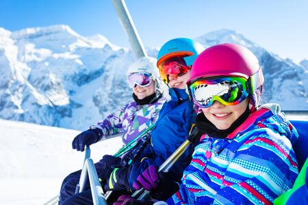Close portrait of three smiling happy girls on chairlift on ski resort with sunny mountain peaks on background Stockfoto