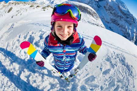 Wide angle fun portrait from above of smiling skier girl with ski look up standing on the slope in pink mask and color glasses