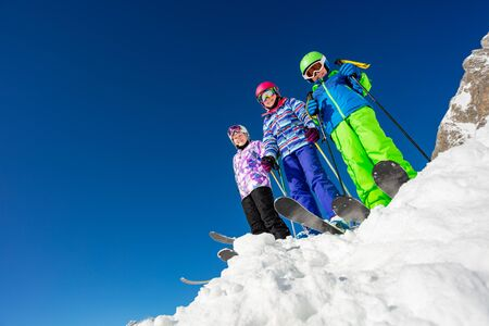 View from below of a group of three kids stand on the mountain top in snow wearing ski colorful outfit over blue sky Stock fotó