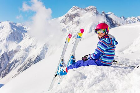 Cute child in bright sport outfit sit on the snow pile in the mountain over high peaks look back to camera Stockfoto