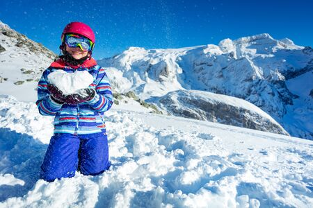 Smiling happy cute girl in ski outfit mask and helmet show love concept holding snow shape in heart standing on knees with mountains on back