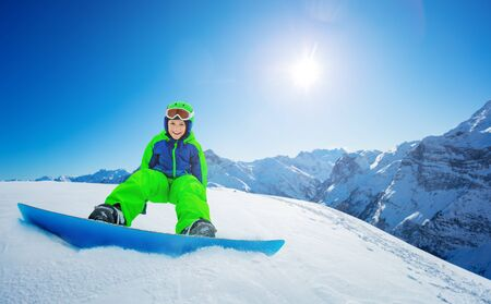 Cute little boy sit on snowboard view over blue sky and mountain range tops on the back Banque d'images