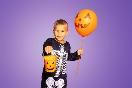 Cute little boy in Halloween costume of skeleton and orange balloon hold candy bucket over purple background