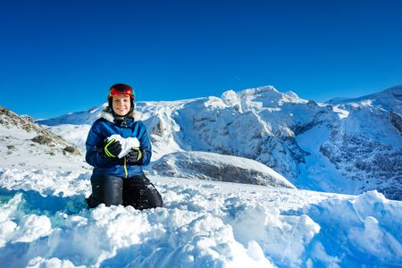 Smiling teenage girl in blue outfit mask and helmet show love concept holding snow shape in heart standing on knees with mountain peak on background