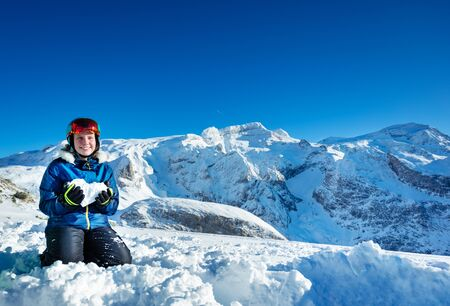 Happy teenage girl hold heart shaped snow showing love concept standing on her knees with mountain peaks on background