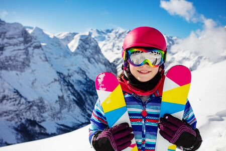 Close-up portrait of cute girl in pink helmet and color hold crossed pair of ski smiling, goggles over high mountain
