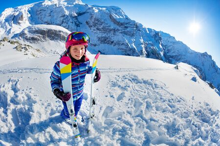 Full height portrait from side of smiling skier girl with ski standing in snow over mountain summit view wear pink mask and color glasses