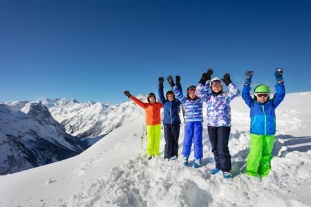 Big group of ski children stand on snow rise hands cheerfully smiling over mountain range peaks in colorful sport outfit Stockfoto