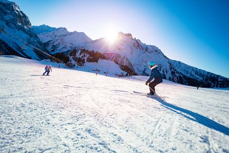 Group of kids ski down before sunset on Alpine mountain slope Stockfoto