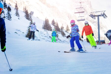 Five kids ski on the Alpine slope as part of the school group one after another with mountains and lift on background