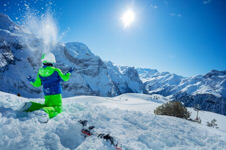 Portrait of cute kid sitting resting after skiing in snow over sunny mountain panorama copy space