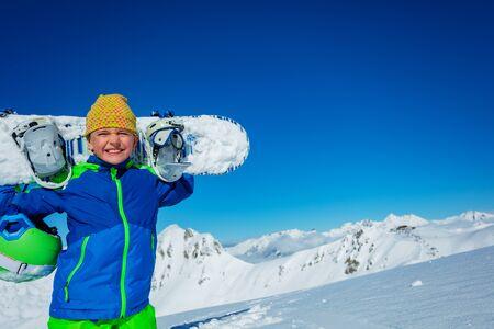 Fermer le portrait d'un garçon tenant un snowboard et un chapeau décontracté sur les épaules au-dessus du panorama de la montagne par beau temps