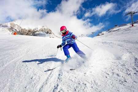 Action high speed motion of the girl ski downhill in the mountains Foto de archivo