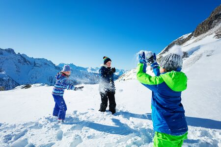 Group of children play snowball fight view behind boy shoulder with snowballs and snow in the air over mountains