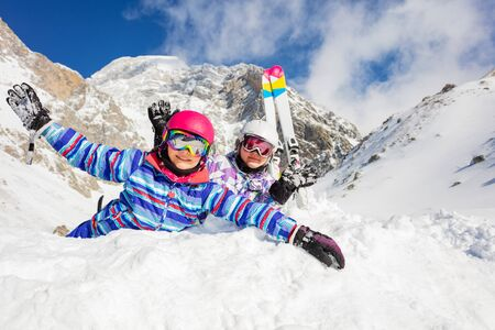 Happy girls lay in snow having ski on background near sister lifting hands with joy and smile Banque d'images