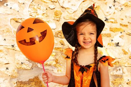 Little girl on Halloween portrait with orange balloon costume smiling looking to camera