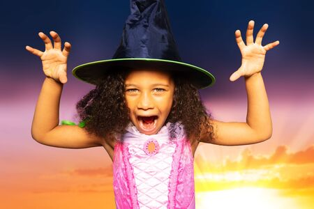 Close portrait of a cute little girl in Halloween dress and witch hat show spooky gesture over sunset background