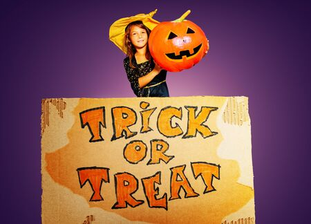 Big Halloween trick of treat sign portrait of a girl in costume with pumpkin over purple background