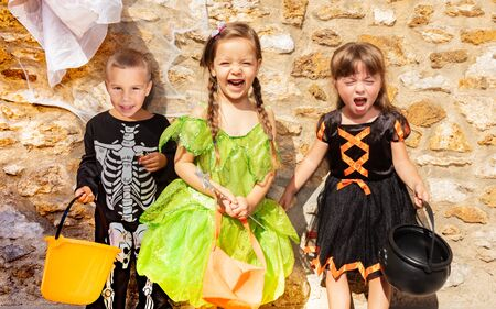 Group of little kids boy and two girls stand together in Halloween costumes, dresses over the stone wall with candy buckets Zdjęcie Seryjne