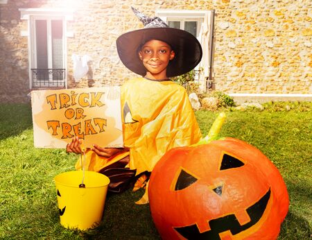 Cute handsome little black boy on Halloween sit on the lawn with pumpkin and trick or treat sign