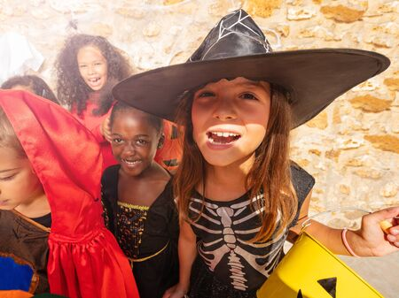 Portrait of a girl in the group of Halloween costume dressed kids standing together with buckets of candies