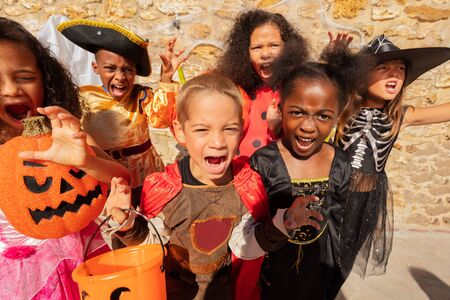 Many kids scream and look at camera in Halloween costumes standing together in a group of friends