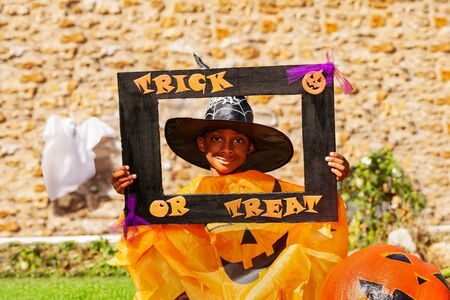 Halloween portrait of a black smiling handsome boy child in spooky costume with pumpkin hold trick or treat frame Zdjęcie Seryjne