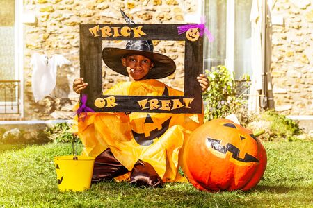 Halloween portrait of a black handsome boy in spooky costume with pumpkin hold trick or treat frame