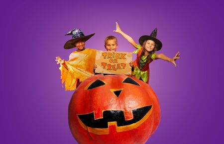 Group of three children in costumes with trick or tread sign on huge Halloween scary pumpkin purple background