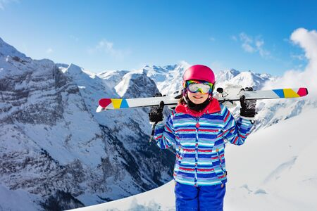 Close portrait of young smiling girl in colorful outfit, pink helmet and color glasses hold ski on her shoulders view over mountain summit on back
