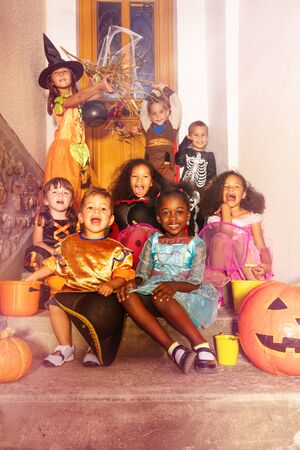 Large diverse group of spooky looking kids in Halloween costumes sit on the stairs of the door of the house