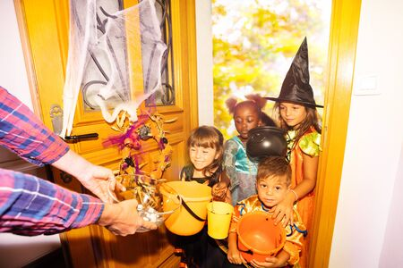 Large group of children Halloween costumes stand in the door with orange buckets for candies receive sweets from adult
