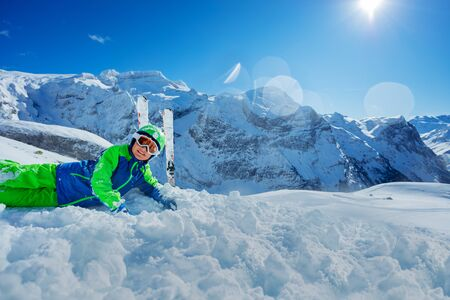 Cute boy having fun resting in snow over sunny mountain panorama copy space