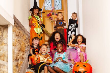 Halloween group kids portrait sit together boys with girls on the stairs near house door in costumes holding pumpkin, buckets scream and smile