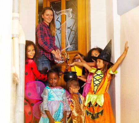 Halloween lifestyle scene with group of children in costumes receive candies from woman standing near house door together Zdjęcie Seryjne