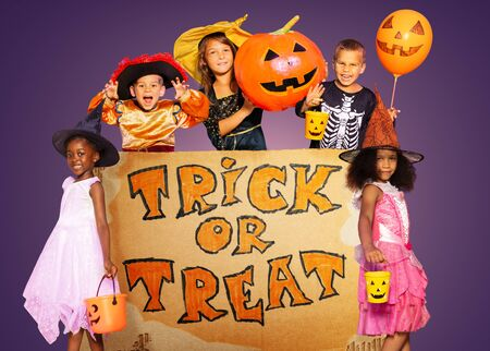 Big Halloween trick of treat sign with large group of kids around in costumes, pumpkin, buckets and balloons