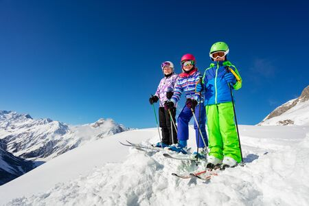 View from below of a group of three children friends boy and girls stand on the mountain top in snow wearing ski outfit over sky