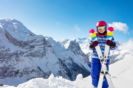 Portrait of cute girl in pink helmet and color hold crossed pair of ski smiling, goggles over high mountain