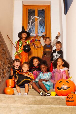 Group of many diverse kids in Halloween costumes sit on the stairs with pumpkin, buckets smiling and looking at camera