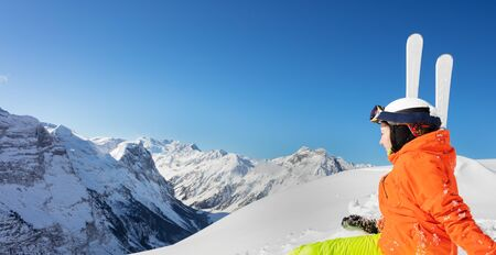 Back portrait of a cute teenage girl in orange bright sport outfit with ski over high mountain range peaks and blue sky